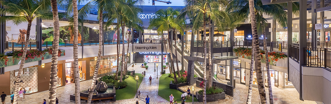At dusk, visitors to Ala Moana stroll through an outdoor atrium lined with palm trees.