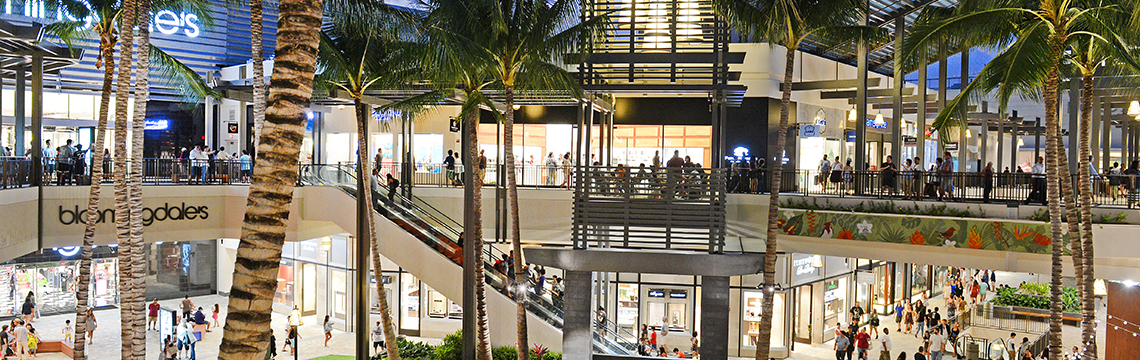 Crowds of visitors at the Ala Moana shopping center stroll through an outdoor atrium